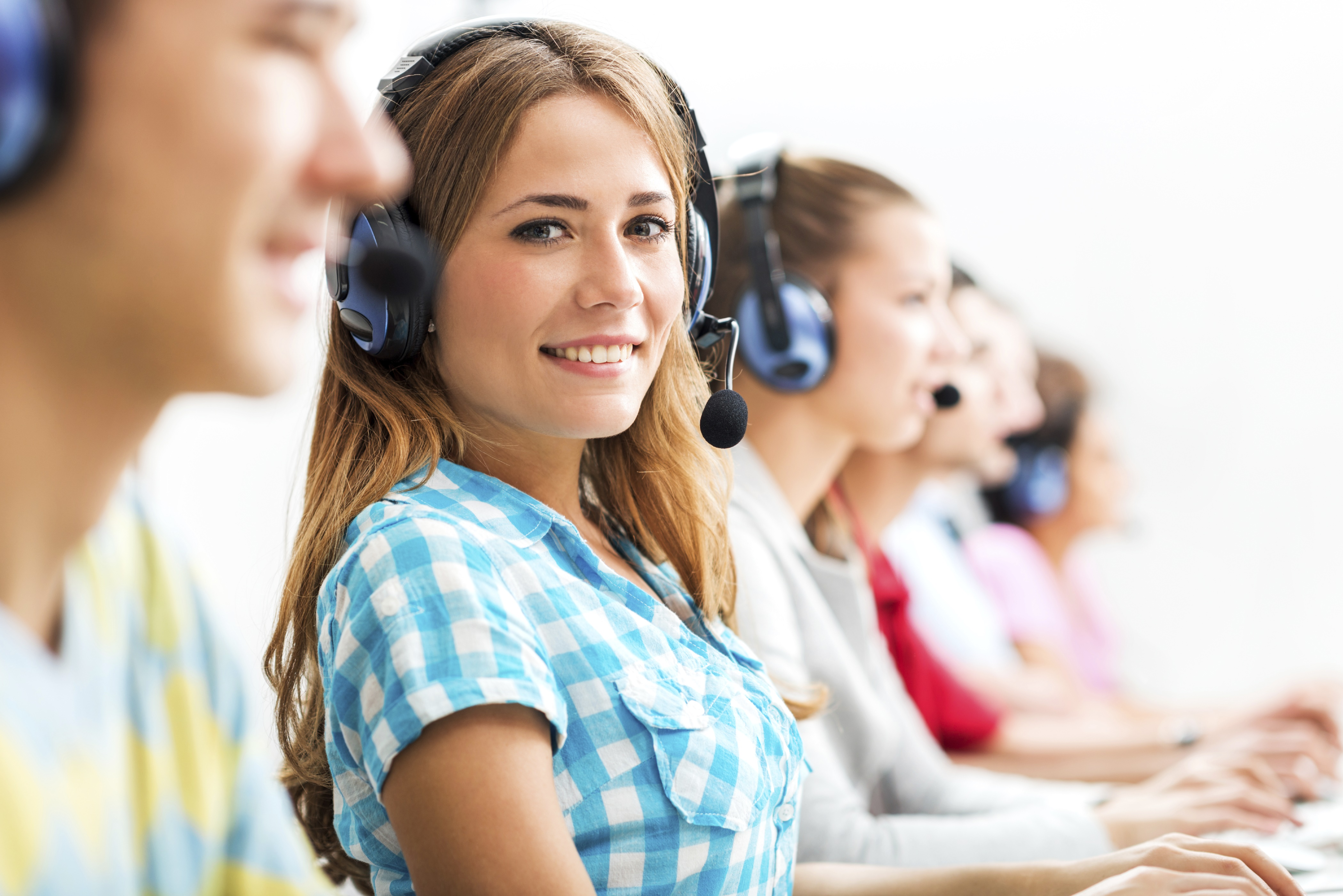 Group of young students sitting in a row at a computer class wearing headphones. Focus is on smiling young woman looking at the camera.